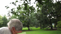 Attractive baby boomer couple sit on a bench together at a park. Medium shot Stock Footage