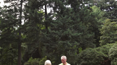 Baby boomer couple walk in park together. - stock footage