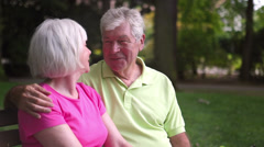 Adorable baby boomer couple romance on a park bench. Medium Shot. - stock footage