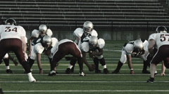 Football players run a running play from the line Stock Footage