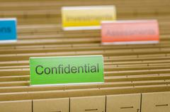 Hanging file folder labeled with confidential Stock Photos
