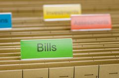 Hanging file folder labeled with bills Stock Photos
