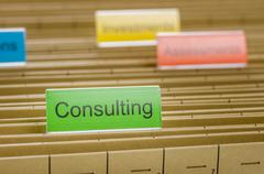 hanging file folder labeled with consulting - stock photo