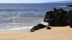 Hawaii waves crashing sandy beach black rock Stock Footage