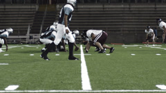 A football player gets tackled while running Stock Footage