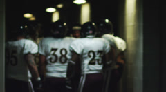 A football team in a circle gets pumped-up in the tunnel before the game Stock Footage