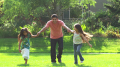 A father runs through an open green field with his two daughters on a sunny day Stock Footage