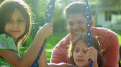 Father pushes his two daughters on a tire swing in a park. Stock Footage