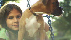 Little girl holds a puppy while standing in the middle of a tire swing. Stock Footage