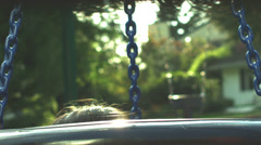 Little girl and puppy pop up through middle of tire swing then go back down. - stock footage
