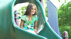 Adorable little girl goes down a slide right into her fathers arms. Stock Footage