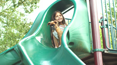 Adorable boxer puppy goes down a park slide. Stock Footage