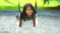 Adorable little girl swings on her belly. - stock footage