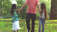 Adorable family walk through a park with leaves on the ground. - stock footage