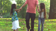 Stock Video Footage of Adorable family walk through a park with leaves on the ground.