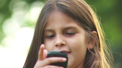 Adorable little girl talks on a cell phone. Stock Footage