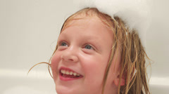 A young girl laughs and smiles in bathtub while covered with suds on her head Stock Footage
