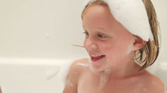 A little girl washes herself with a washcloth while taking a bubble bath - stock footage