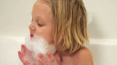 A baby and a little girl make a beard out of suds while sitting in a bubble bath - stock footage