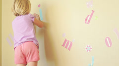 A young girl puts decals on her bedroom wall Stock Footage