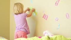 A young girl puts stickers on her bedroom wall - stock footage
