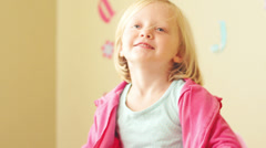 A young girl in a pink sweatshirt flexes her muscles Stock Footage