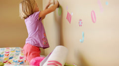 A young girl sits on her bed and puts stickers on her wall Stock Footage