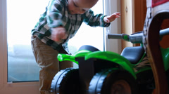 A toddler playing with a toy four wheeler Stock Footage