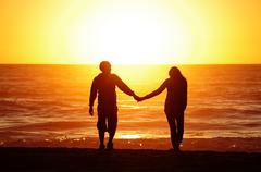 loving couple beach sunset - stock photo