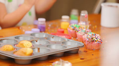 Two young girls help their mother put frosting and sprinkles on cupcakes - stock footage