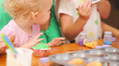 A mother kisses her young girls while they make cupcakes Stock Footage