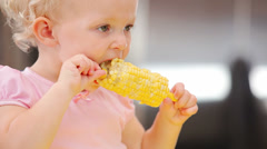 A young girl sits in her high chair and eats corn off of the cob Stock Footage
