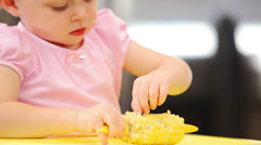 A young girl sits in her high chair and eats corn off of the cob - stock footage