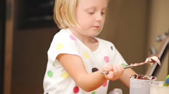 A young girl puts frosting on a cupcake while helping her mother - stock footage