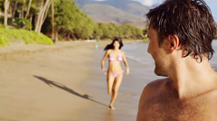 Man gives woman piggyback ride on the beach. Medium shot. Stock Footage
