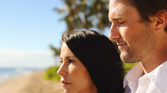 Attractive couple look out into the distance on a beach. Stock Footage
