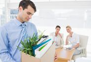 Stock Photo of Businessman carrying his belongings with colleagues in background