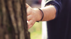 A series of shots of a man and woman walking around a tree and flirting Stock Footage