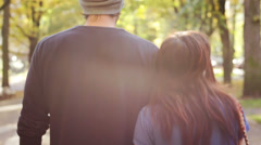 The camera follows a couple who hold each other as they walk through the park - stock footage