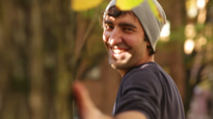 A man and his hand smiling and flirting with the camera as he circles a tree - stock footage