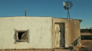 Stock Video Footage of Abandoned Desert Ranch Adobe House with Windmill