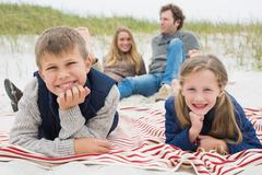 Happy family of four at a beach picnic - stock photo