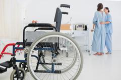 Lääkäri auttaa potilasta kävelemään pyörätuolin edustalle Kuvituskuvat