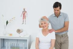 Senior woman getting the neck adjustment done Stock Photos