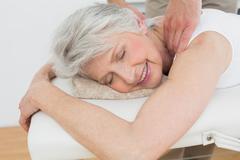 Physiotherapist massaging a senior woman's shoulder Stock Photos