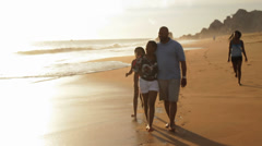 A family takes a stroll along a beach in Mexico Stock Footage