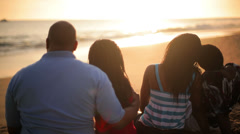 Attractive African American family watches sunset on beach - stock footage