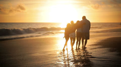 Happy family walk down the beach away from the camera Stock Footage