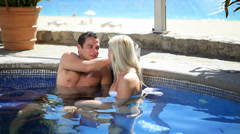 A cute couple share drinks and conversation in a hot tub Stock Footage