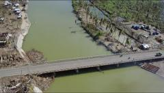 Aerial of a devastated area with a river and bridge crossing Stock Footage